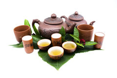 Clay teapot and cups with tea leaves Stock Photos