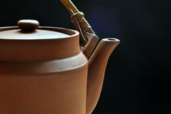 Clay teapot on dark blue background. A simple clay teapot in front of an uneven dark blue background Stock Image