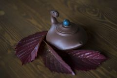 Clay teapot with dragon head in chinese style with red grape leaves at dark wooden background royalty free stock photos