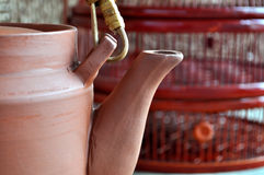 Clay teapot in front of bamboo basket. A clay teapot in front of a painted bamboo basket Stock Images