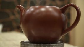 Clay teapot with hot tea on a heated base steaming.  stock footage