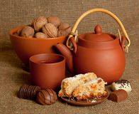 Clay teapot with sweets Stock Photo