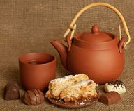 Clay teapot with sweets Stock Photos