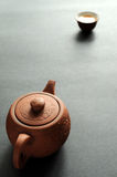 Clay teapot and teacup. A clay teapot with a blurred teacup as background Royalty Free Stock Photos