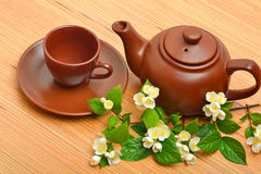 Clay teapot, teacup, saucer and jasmine flower twig on wood Royalty Free Stock Images
