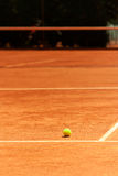 Clay Tennis Court with Ball. Tennis Ball stands on a Court during a game (excellent background for Tennis Events Media Stock Photos