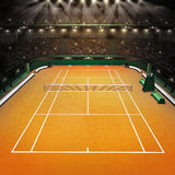 Clay tennis court and stadium full of spectators with spotlights Royalty Free Stock Image
