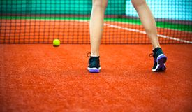 Clay tennis court with Tennis player legs. Close-up rear view of beautiful woman in sports clothing playing tennis on court Stock Photos