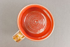 Clay terracotta mug top view. View from top of a clay terracotta mug, bright vivid colours, intensive red. Very cheerful. The cup was bought second hand and does royalty free stock image