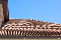 Clay tile roof in florida against clear blue sky. Peak of a clay tile roof with half round shingles against a blue sky in southern florida Royalty Free Stock Photo