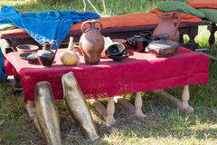 Clay utensils on table with a red cloth coverings Stock Images