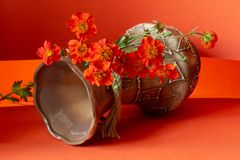 Vase with flowers. Clay vase with a pattern and red flowers on a red background stock images