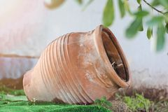 Clay vase, pot, for growing flowers, trees lies on its side upside down on the street. Athens, Greece stock photography