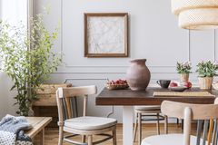 Clay vase on the table in a dining room interior with a plant, chairs and art on a wall royalty free stock photos
