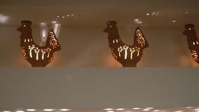 Clay vases in the form of roosters on the shelf. The candle is burning inside. home interior and comfort.  stock video footage