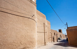Clay walls of the narrow street with parked cars ourtyard Stock Photos
