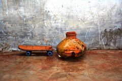 Clay water pot (Gharra) and an old skateboard Stock Image