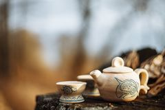 Clay white teapot with blue pattern and two drinking bowls in the forest on the stump. Handwork stock photography