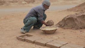 Clayman making bricks stock video