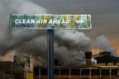 Clean air ahead slogan on the road sign in front of factory Royalty Free Stock Image