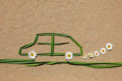 Clean air concept: automobile. A car made of grass is situated on a sandy ground stock image