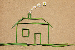 Clean air concept: house. A house made of grass is situated on a sandy ground royalty free stock images
