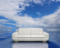 Clean air environment concept. White sofa on blue sky cloudscape reflection surface Stock Images
