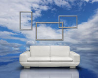 Clean air environment concept. White sofa and silver frames on blue sky cloudscape reflection surface Royalty Free Stock Image