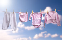 Clean baby girl clothes on the outdoor clothesline Stock Photos