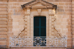 Clean balcony in front of closed green shutters. Photo was taken in Malta Stock Photo