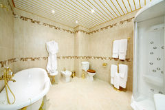 Clean bathroom with bath, shower cabin, toilet and bidet Stock Photos