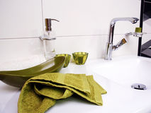 Clean bathroom sink with green towel. Detail stock photo