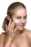Clean beauty portrait of a blond applying a cream Stock Photography
