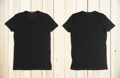 Clean black t-shirt. S back and front on wooden background. Advertising and fashion concept. Mock up royalty free stock photo