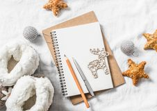 Clean blank notepad, christmas ornaments, wooden reindeer, toys, home ugg boots on a light background, top view Royalty Free Stock Image