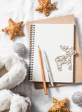 Clean blank notepad, christmas ornaments, wooden reindeer, toys, home ugg boots on a light background, top view Royalty Free Stock Images