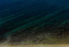 Clean blue sea, with a pebbly-rocky beach. Clean sea, with a pebbly-rocky beach and seaweed royalty free stock image
