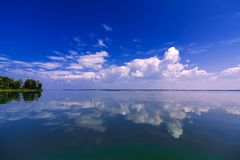 Clean blue sky reflected in calm water on summer day Stock Photo