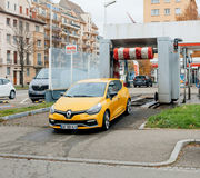 Clean car leaving car wash. STRASBOURG, FRANCE - DEC 2, 2016:Clean Renault Clio sport yellow car leaving automatic car wash royalty free stock image