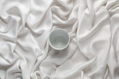 Clean ceramic empty coffee cup on the silk white fabric. Top view. Stock Image