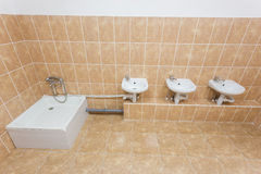 Clean children washroom with sinks and water-closet in kindergarten. Front view. Royalty Free Stock Photos