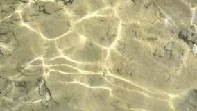 Clean clear water through which the sun shines and you can see the bottom. Of sand and stones stock footage