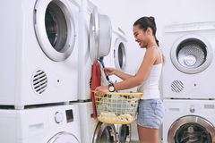 Clean clothes. Cheerful female student taking clean clothes out of washing machine Stock Photos