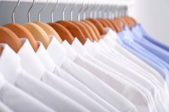 Clean clothes on hangers after dry-cleaning. Closeup Royalty Free Stock Photo
