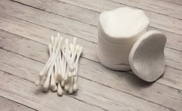 Clean cotton pads and chopsticks on a wooden background stock photography
