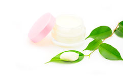 Clean cream facial. Close-up of a face cream with a green leaf Royalty Free Stock Image