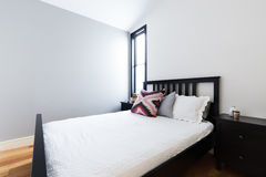 Clean crisp modern bedroom with light grey feature wall Royalty Free Stock Images