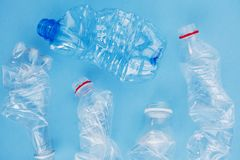 Clean crumpled plastic water bottles ready for recycling isolated on blue background, top view, flat lay. Waste management concept royalty free stock photography