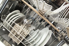 Clean Dishes. A dishwasher with clean dishes and one empty drawer or shelf Royalty Free Stock Image