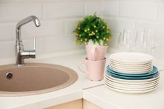 Clean dishes on counter near kitchen sink. Indoors stock photography